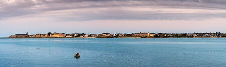 A panorama view of the coastal town of Roscoff in Brittany at sunset calm ocean and copy space in the foreground