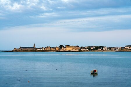 A view of the coastal town of Roscoff in Brittany in the evening with calm ocean and copy space in the foreground