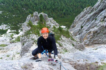 A woman in her twenties climbing a steep Via Ferrata in the Dolomites of Alta Badia Stock fotó