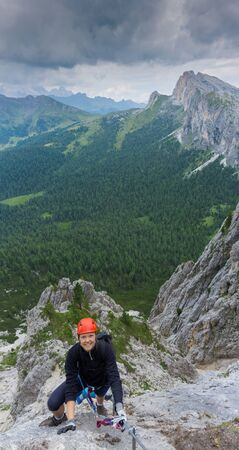 A vertical panorama of a woman in her twenties climbing a steep Via Ferrata in the Dolomites of Alta Badia