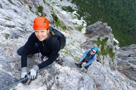 A man and woman in their twenties climb a steep Via Ferrata for fun during their holidays Stock fotó
