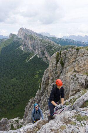 A man and woman in their twenties climb a steep Via Ferrata for fun during their holidays Stock fotó