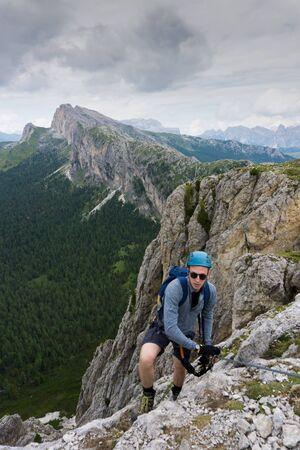 A man in his twenties climbing a steep Via Ferrata in the Dolomites of Alta Badia
