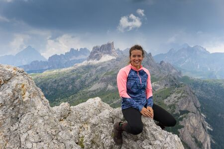 An attractive brunette mountain climber sitting on a mountain peak and smiling