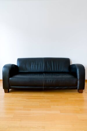 A vertical view of a dark brown leather couch in a minimalist apartment