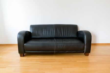 A horizontal view of a dark brown leather couch in a minimalist apartment