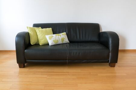 A horizontal view of a dark brown leather couch with three pillows in a minimalist apartment