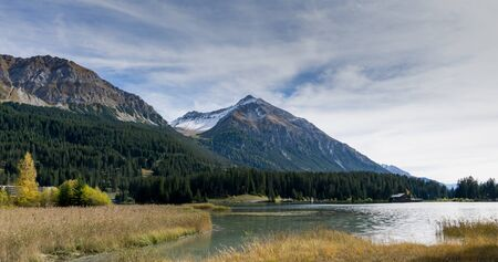 mountain lake landscape in Switzerland in autumn with snowy peaks behind