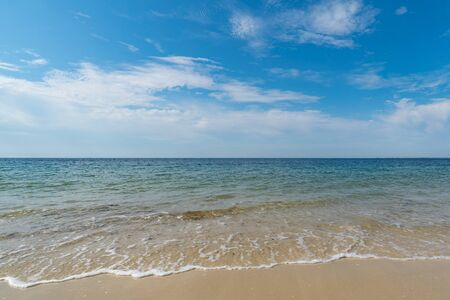 empty tropical beach with gentle waves and a great view over the calm ocean