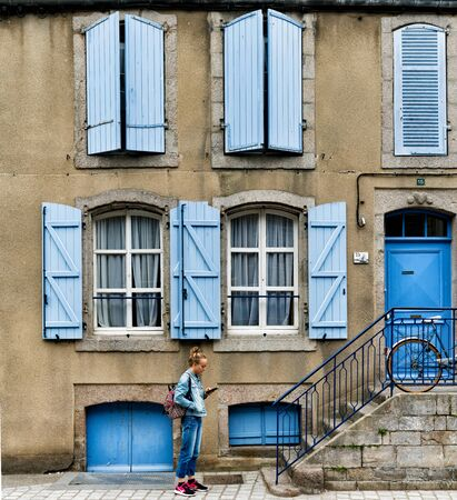 Saint-Vaast-la-Hougue, Manche  France - 16 August, 2019: teenage girl dressed in blue interacting with her cell phone in front of a house with blue shutters and doors