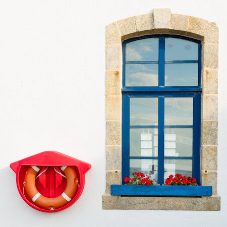 A stone window with blue and bright red rescue ring mounted on a white wall