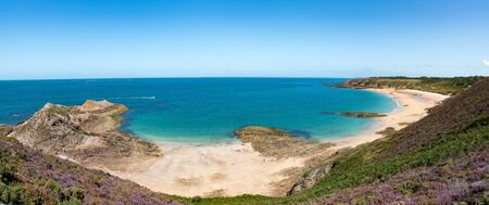 An idyllic wild secluded beach with turquoise water and lilac heath meadows