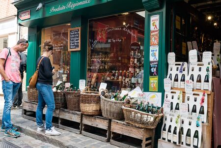 Honfleur, Calvados  France - 15 August 2019: tourist browsing and window shopping at a cider and liquor shop in Honfleur Editöryel