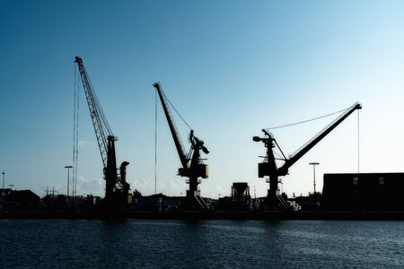 silhouette of three port cranes in a large commercial port under a blue evening sky at twilight