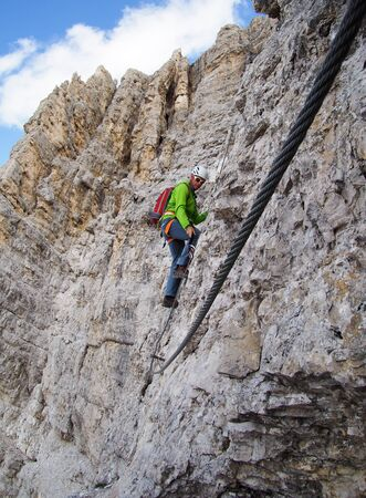 A middle-aged male climber on a steep and exposed rock face climbs a Via Ferrata in Alta Badia in the South Tyrol