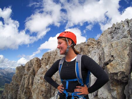 An attractive brunette female climber on a mountain peak in the Dolomites looking to the distance