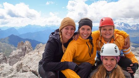 four attractive women mountain climbers hug and smile on a mountain peak after a hard climb in the Italian Dolomites near Cortina dAmpezzo