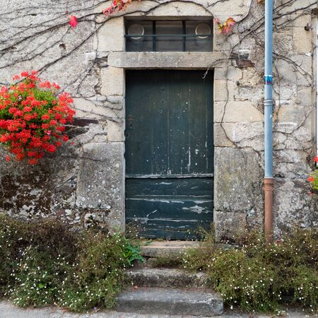 Rochefort-en-Terre, Morbihan / France - 24 August, 2019: old door in a stone house facade with vines and bright red flowers 報道画像