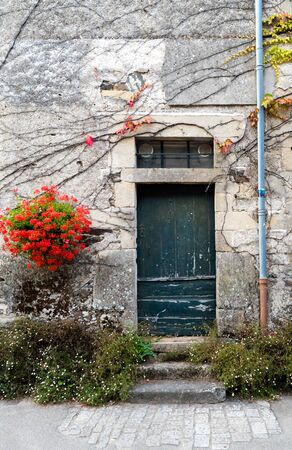 Rochefort-en-Terre, Morbihan  France - 24 August, 2019: old door in a stone house facade with vines and bright red flowers