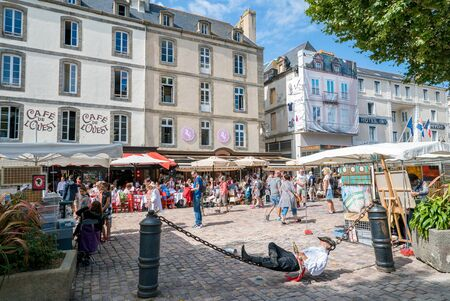 Saint-Malo, Ille-et-Vilaine / France - 19 August 2019: busy summer day in old town Saint-Malo with sleeping pirate and tourists in restaurants and market stalls