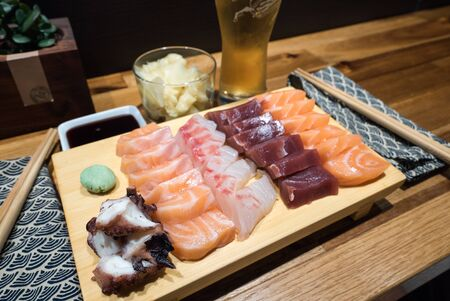 A close up view of a delicious plate of fresh sashimi in a sushi bar with beer and soy sauce and ginger