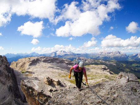 A female mountain climber reaches the summit with great Dolomites landscape behind Stock fotó