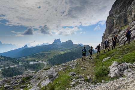 group of mountain climbers hiking up a mountain side to a hard climbing route in the Dolomites of Italy