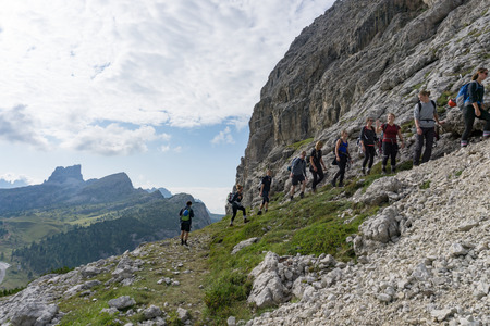 Passo Falzarego, Trentino  Italy - 1 September 2019: group of mountain climbers hiking up a mountain side to a hard climbing route in the Dolomites of Italy