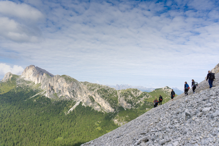 panorama view of a group of mountain climbers hiking up a mountain side to a hard climbing route