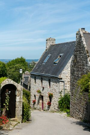 Locronan, Finistere / France - 23 August, 2019: typical Breton stone houses in the picturesque French village of Locronan