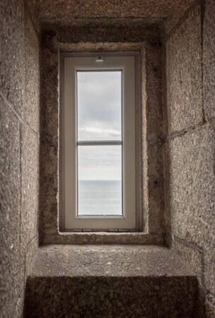 A verticalview of the ocean through a lighthouse window in the stone staircase