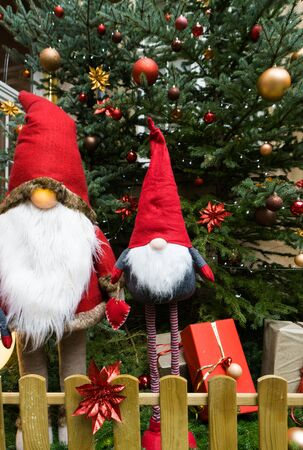 A close up view of Christmas tree with beautiful decorations and large stuffed Santa Claus dolls