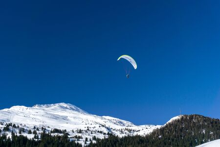 A winter mountain landscape with snowy mountain peaks and a paraglider in the blue sky above