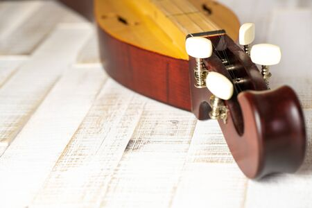 Detail view of an Appalachian mountain dulcimer musical instrument on a rustic white wooden background