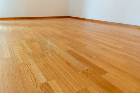 A low angle view of wooden parquet floor in a bright and spacious home Standard-Bild