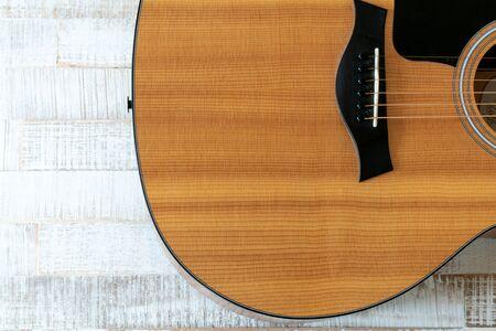 Top-Down-Ansicht der schönen Akustikgitarre auf einem rustikalen weißen Holzhintergrund mit Kopierraum