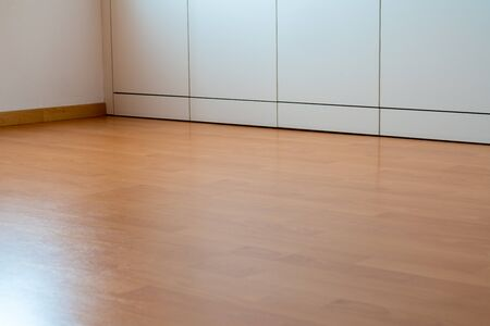 A low angle view of wooden laminate flooring in a bright spacious room with wall-to-wall closet