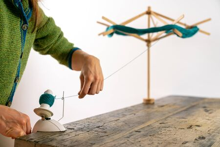 Selective focus view of a caucasian woman working a hand-operated knitting roll to prepare wool thread for knitting
