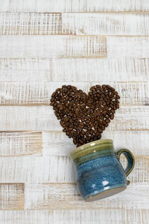 coffee bean heart coming out of a colorful coffee mug on rustic white wood background with copy space