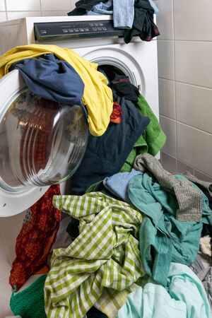 A giant pile of colorful dirty laundry and a washing machine stuffed full with clothes Stok Fotoğraf