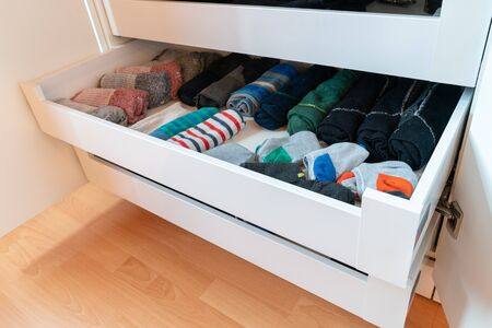 many colorful men's socks in a plain white wooden sock drawer in a large closet
