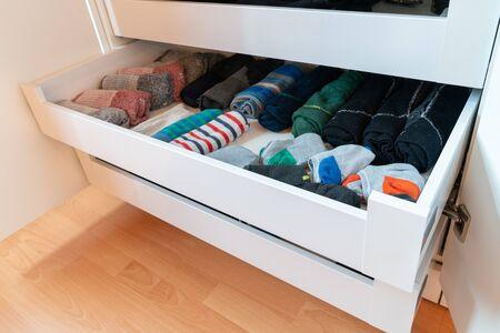 molti calzini da uomo colorati in un semplice cassetto dei calzini di legno bianco in un grande armadio