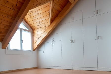 An interior view chalet style room with parquet flooring and wooden beam roof and wall to wall closet Standard-Bild