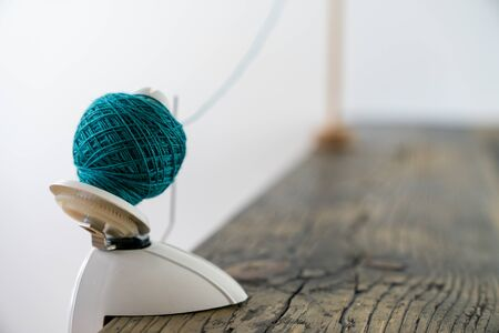 selective focus view of a hand-operated knitting roll or wool thread ball winder and knitting umbrellla