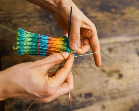 A close up of female hands knitting colorful socks