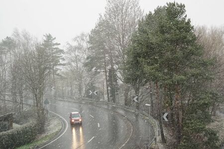 A country road and forest during a snowstorm with heavy winds and snowfall with a red car driving slowly