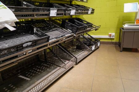 View of empty fruit and vegetable shelves in a European supermarket after buying food supplies