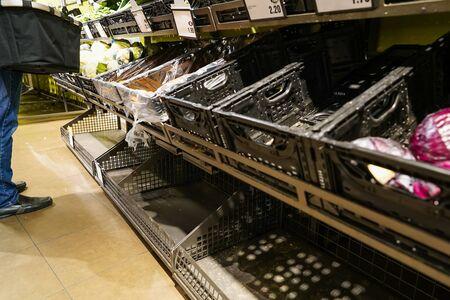 A shopper in European supermarket choosing from limited fresh vegetables