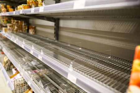 Many empty shelves with few canned goods left in a European supermarket because of panic shopping because of Covid-19 virus