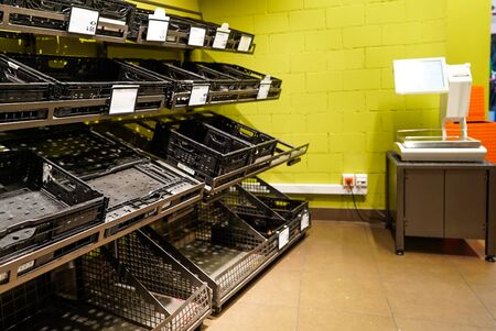 View of empty fruit and vegetable shelves in a European supermarket after buying food supplies because of Covid-19
